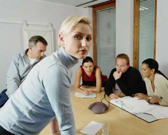 Eine Frau schaut unverwandt in Kamera, Meeting, Business