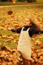 Mädchen mit ausgebreiteten Armen im Herbst, Herbstlaub,