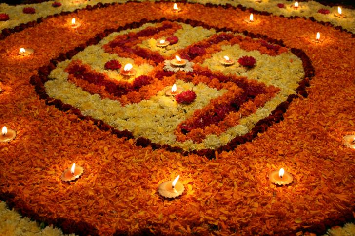 Indische Swastika aus Blütenblättern und Kerzen