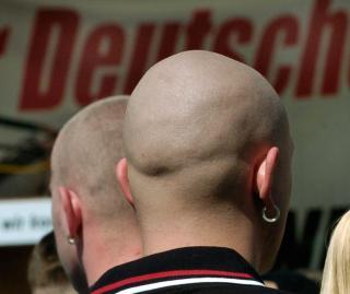 Kahlgeschorene Demonstranten stehen in Berlin in einer Gruppe von rechtsextremen NPD-Anhängern