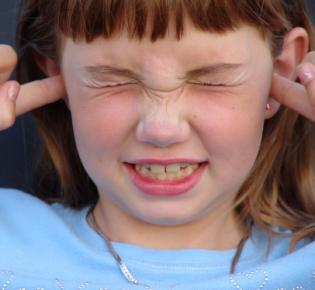 Mädchen hält sich die Ohren zu