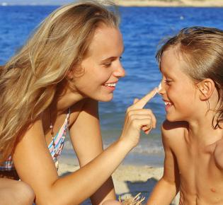 Mutter cremt ihren Sohn mit Sonnencreme ein