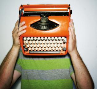 Mann mit Schreibmaschine vor dem Kopf