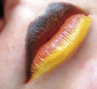 Detailaufnahme von schwarz rot gold geschminkten Lippen